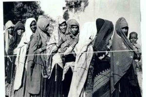 Women wait to cast their votes in Narela (Delhi) in the first elections